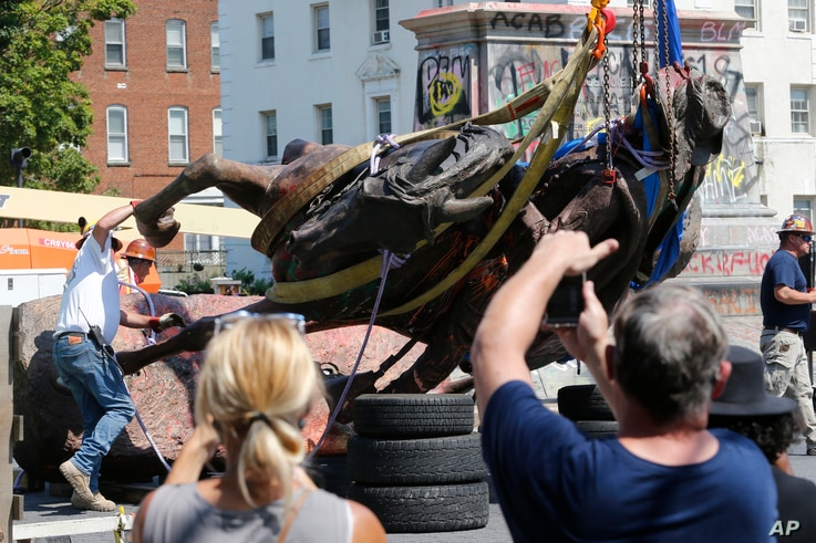 Crews lower the statue Confederate General J.E.B. Stuart in preparation for transport after removing it from it's pedestal on…