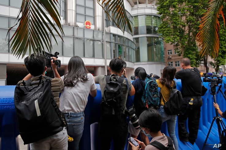 Journalists take pictures and video over the water-filled barriers after an opening ceremony for the China's new Office for Safeguarding National Security in Hong Kong, July 8, 2020.