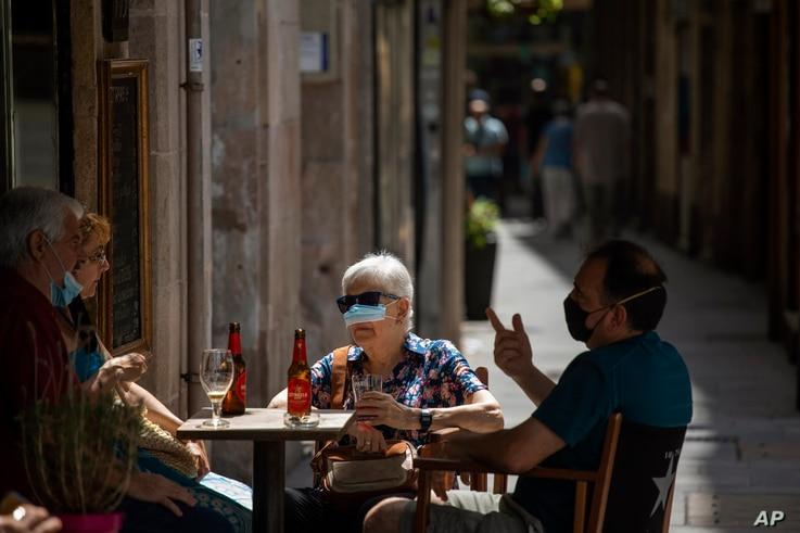 A woman, partially wearing a face mask, sits in a terrace bar in Barcelona, Spain, Thursday, July 9, 2020. Authorities in…