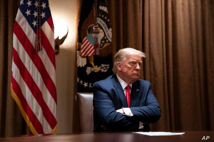 President Donald Trump listens during a meeting with Hispanic leaders in the Cabinet Room of the White House, July 9, 2020.