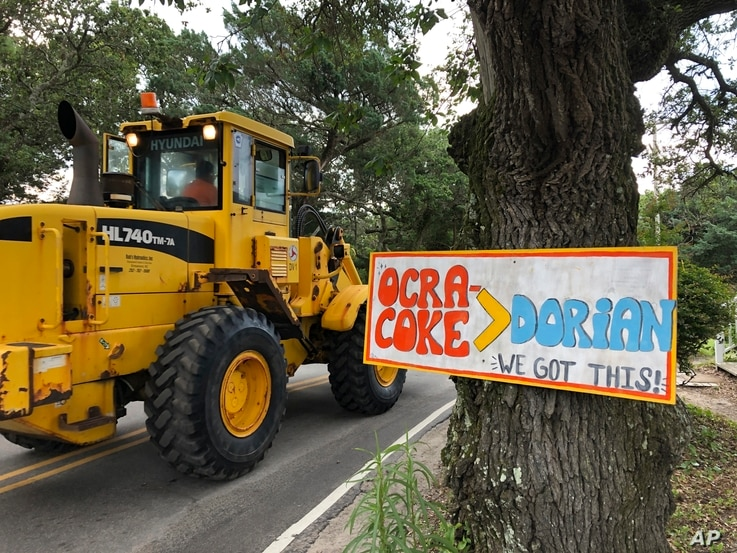 Construction equipment passes a homemade sign posted in the wake of Hurricane Dorian on North Carolina's Ocracoke Island on June 25, 2020.