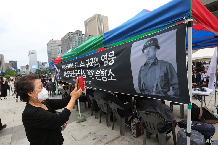 A mourner takes photos of the late South Korean Army Gen Paik Sun-yup at a memorial altar for him at the Gwanghwamun Plaza in Seoul, South Korea, July 12, 2020.
