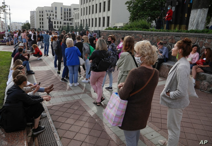 People stand in a line outside the national elections commission to sign complaints about the removal of Viktor Babariko and…