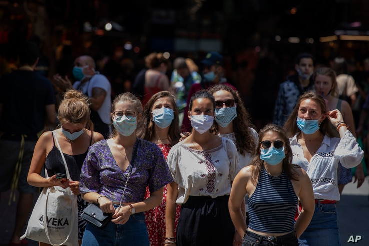 Tourists wearing face masks wait to cross a road in downtown Barcelona, Spain, July 16, 2020.