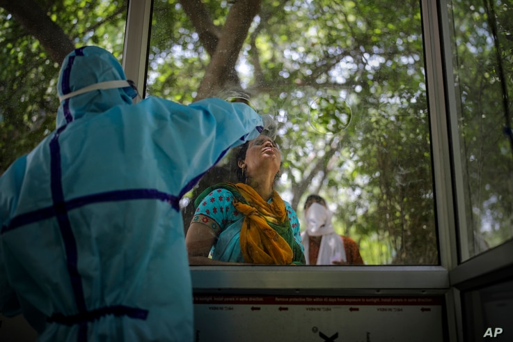 A woman gets a nasal swab taken to test for the coronavirus in Noida, outskirts of New Delhi, India, Thursday, July 16, 2020. …