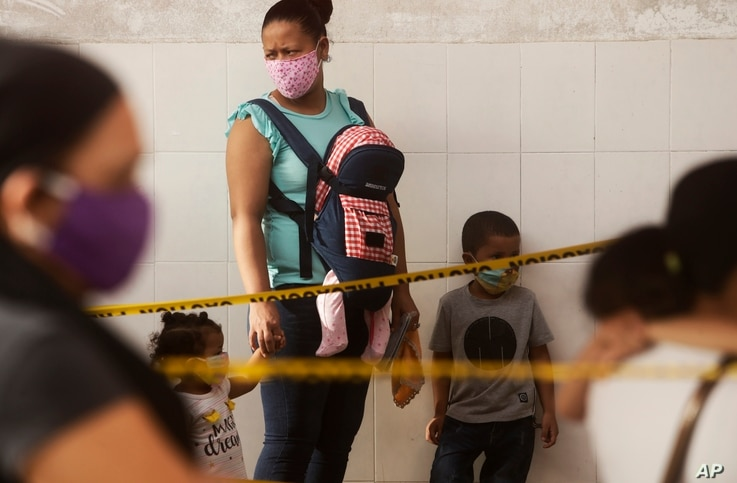 A woman with her children, wearing face masks amid the spread of the new coronavirus, wait at a health center for flu shots in…