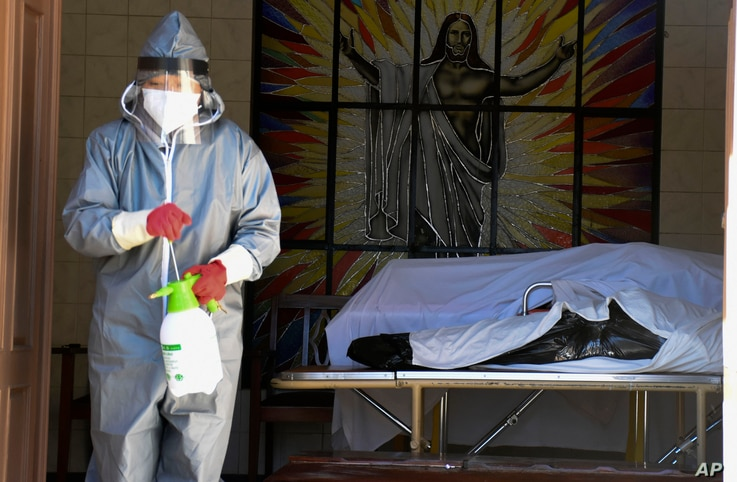 A health worker disinfects the area next to a coffins with the remains of a recently deceased resident of the San Jose nursing…