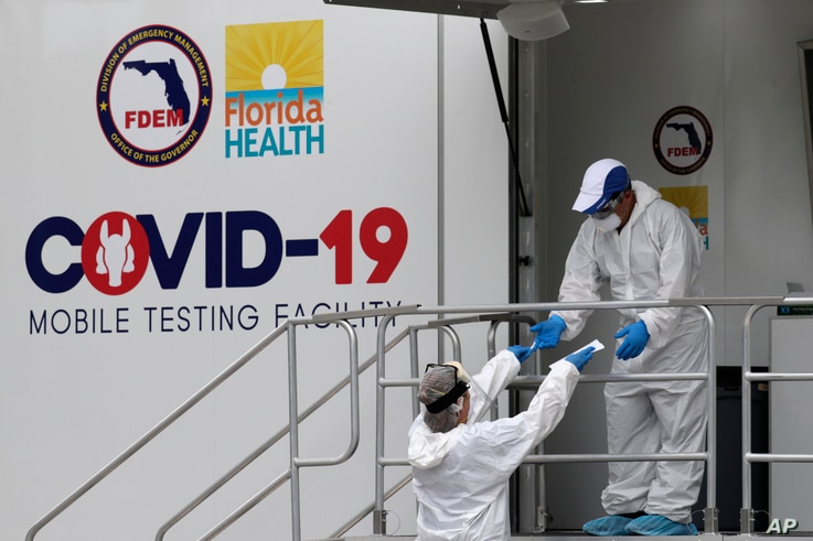 Health care workers work at a walk-up COVID-19 testing site during the coronavirus pandemic, July 17, 2020, in Miami Beach, Florida.