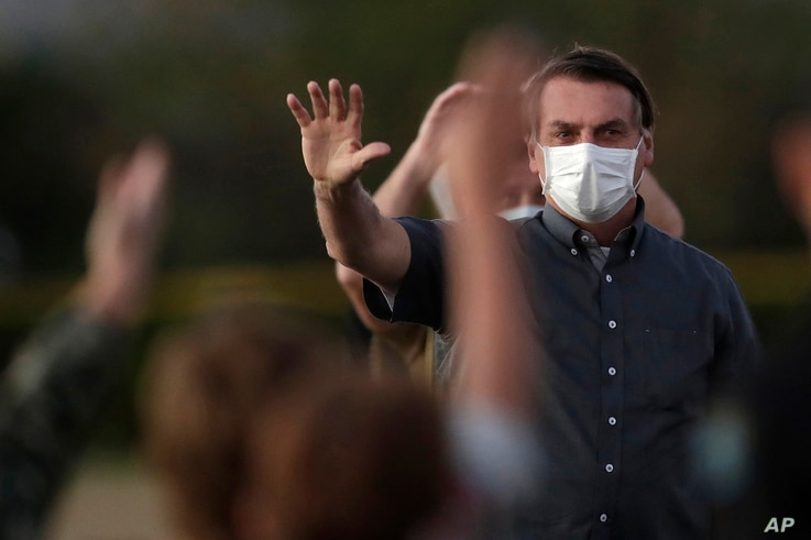 Brazil's President Jair Bolsonaro who is infected with COVID-19, wears a protective face mask as he waves to supporters during…