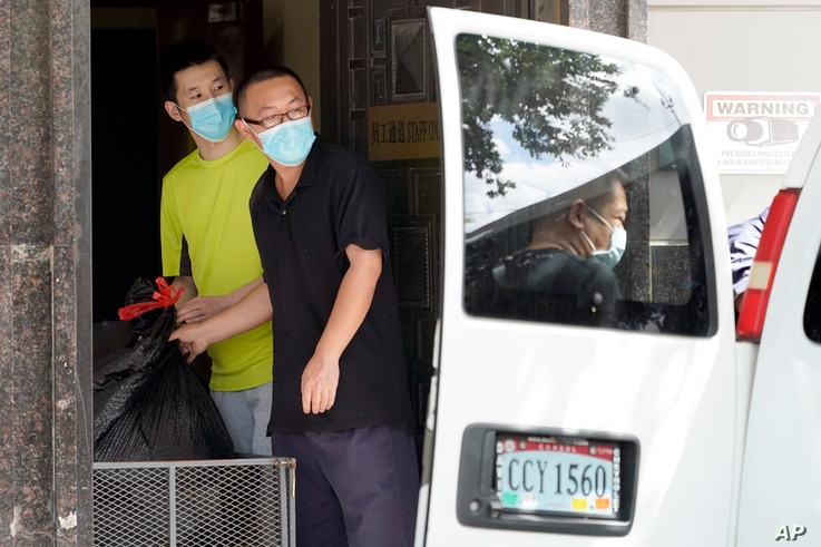 People remove bags from inside the Chinese Consulate to load into a van Thursday, July 23, 2020, in Houston.  China says …