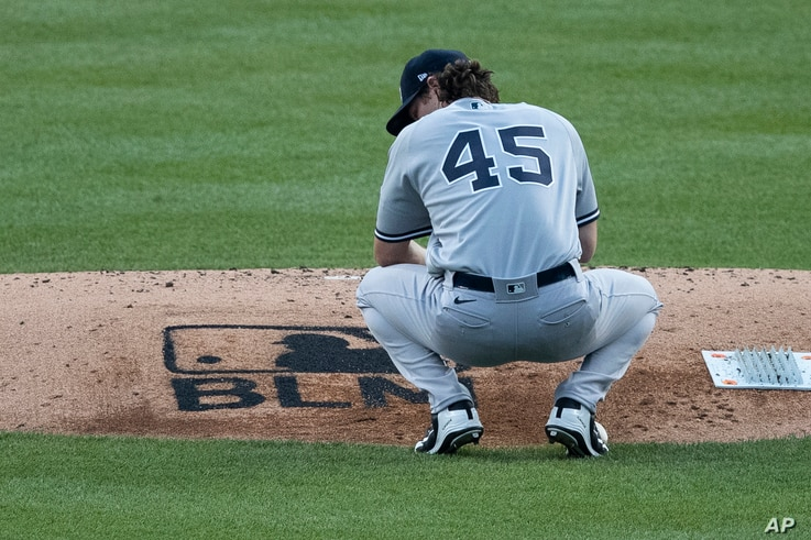 "New York Yankees starting pitcher Gerrit Cole pauses and looks down at the ""Black Lives Matter,"" stenciled on the pitchers…"