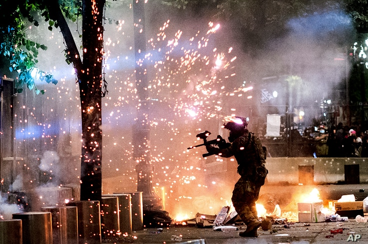 A federal officer fires crowd control munitions at Black Lives Matter protesters at the Mark O. Hatfield United States Courthouse, July 24, 2020, in Portland, Oregon.