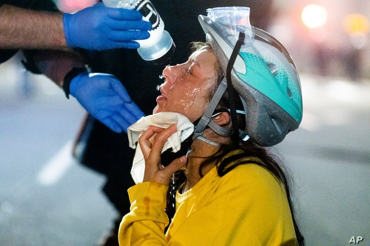 A medic treats Black Lives Matter protester Lacey Wambalaba after exposure to chemical irritants deployed by federal officers at the Mark O. Hatfield United States Courthouse, July 24, 2020, in Portland, Oregon.