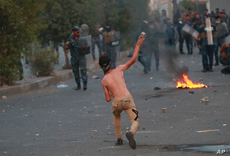 An anti-government protester throws a stone toward security forces during ongoing anti-government protests near Tahrir square,…