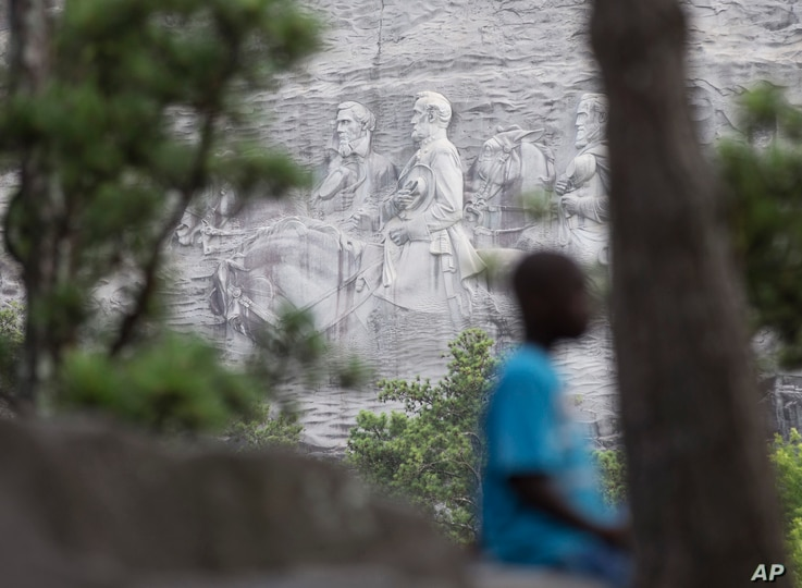 FILE - In this Tuesday, June 23, 2015, file photo, a youngster plays on a rock in front of the carving on Stone Mountain, in…