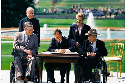 President George H. W. Bush signs the Americans with Disabilities Act of 1990 into law. Pictured (left to right): Evan Kemp, Rev Harold Wilke, Pres. Bush, Sandra Parrino, Justin Dart. July 26, 1990.