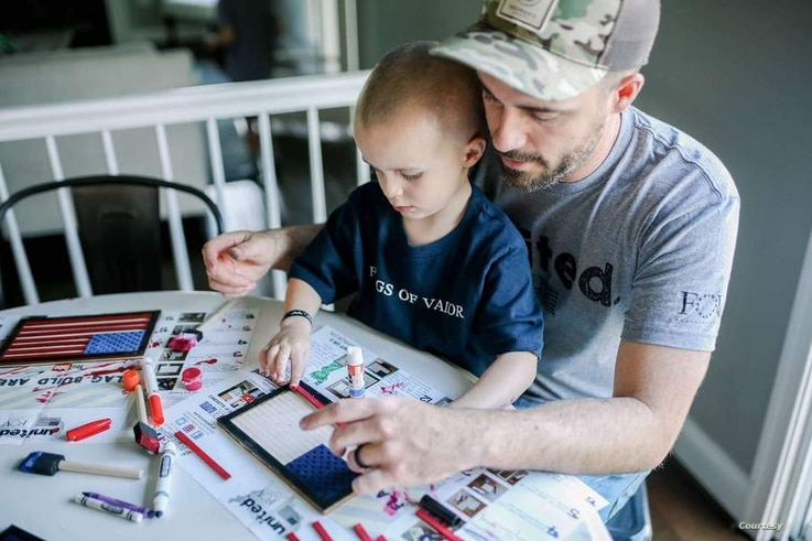 A father and son work together on a children's flag kit from Flags of Valor in Ashburn, Virginia. (Photo courtesy Flags of Valor