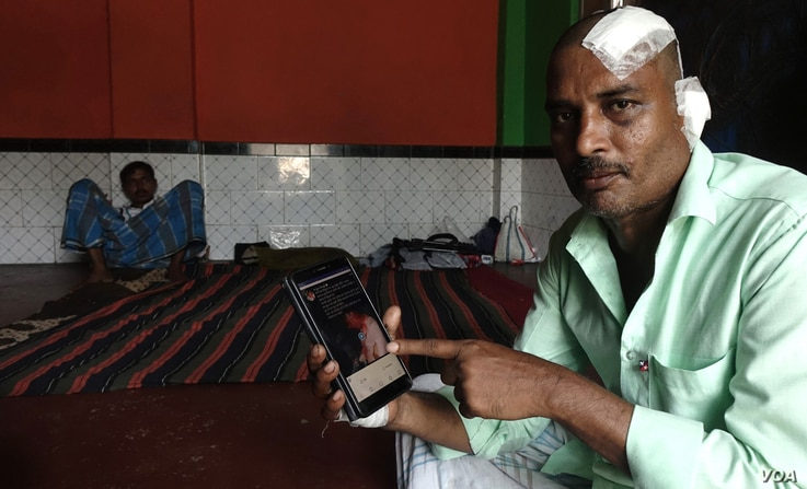 Manzoor Alam, a Muslim jute mill laborer, shows BJP MP Arjun Singh's Facebook post. Alam was beaten up by a Hindu mob in Telinipara. Singh posted a photo of bloodied Alam on Facebook and claimed that he was a Hindu who had been beaten up by Muslims. Singh is being investigated. (Alex Simon/VOA)