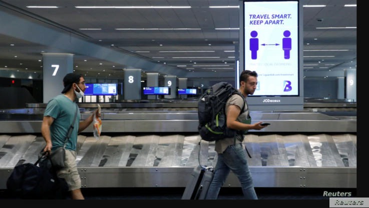 Travelers at LaGuardia Airport, New York, pass a sign alerting them to social distance during the outbreak of the coronavirus, June 29, 2020. Airports across the country have been eerily quiet since US airlines travel has dropped during the coronavirus pandemic. (REUTERS)