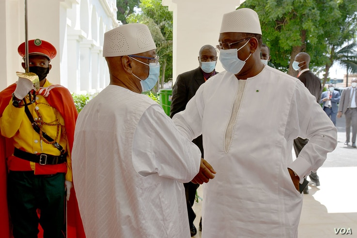 Mali's President Ibrahim Boubacar Keita, right, and Senegal's President Macky Sall bump elbows outside a Bamako hotel, July 23.