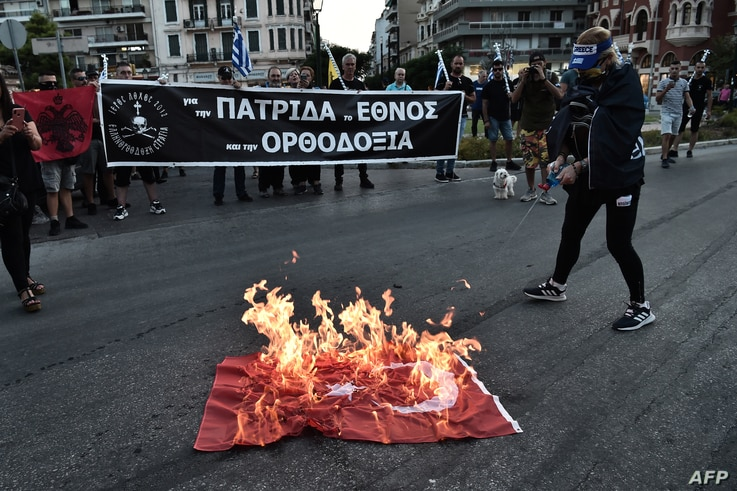 Protesters burn a Turkish national flag outside of a church during a gathering in Thessaloniki, July 24, 2020, against turning the historic Hagia Sophia in Istanbul to a mosque after serving for more than 80 years as museum.
