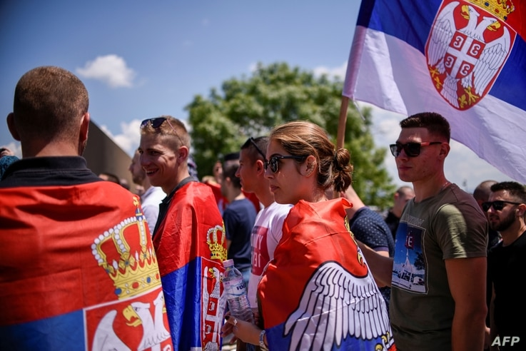 FILE - Serbs holding Serbian flags take part in a ceremony marking the historic Battle of Kosovo, at a memorial in Gazimestan, on the outskirts of Pristina, Kosovo, June 28, 2020.
