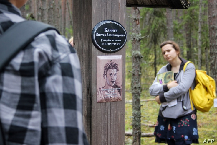 FILE - People visit the Sandarmokh memorial site, Aug. 5, 2018, located in a pine forest in Russia's Karelia region, where mass graves from the period of Joseph Stalin's purges have been found.