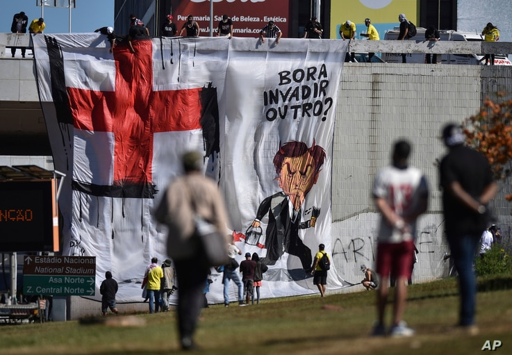 FILE - Demonstrators unfurl a banner with a cartoon image depicting Brazil's President Jair Bolsonaro with a paintbrush, having transformed a red cross into a swastika, during an anti-Bolsonaro protest, in Brasilia, Brazil, June 21, 2020.