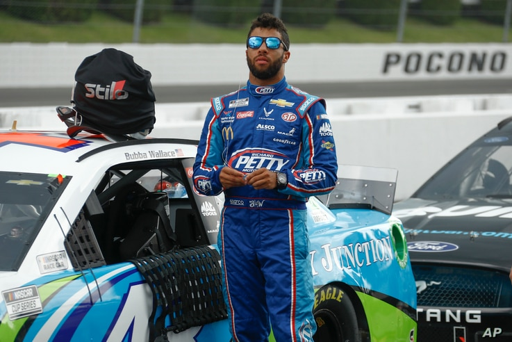 FILE - Bubba Wallace stands by his car before the start of the NASCAR Cup Series auto race at Pocono Raceway, in Long Pond, Pennsylvania, June 28, 2020.