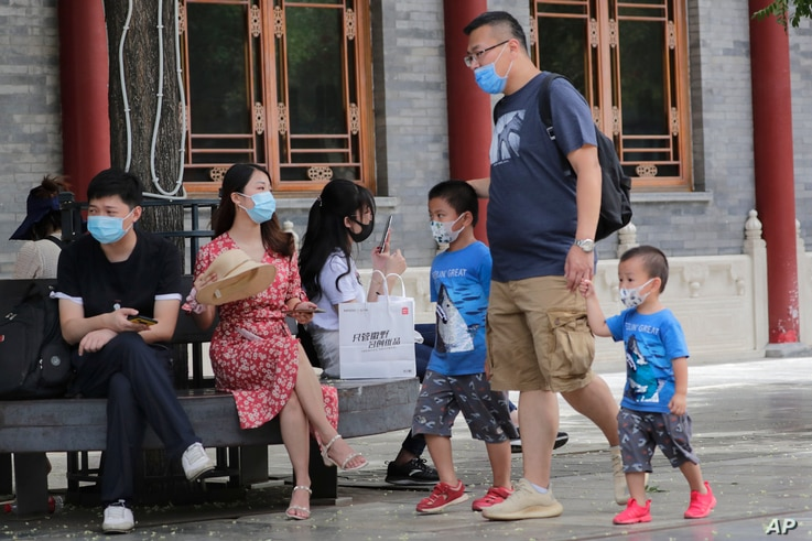 People visit a shopping district in Beijing, July 19, 2020.