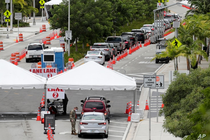 Vehicles wait in line at a COVID-19 testing site at the Miami Beach Convention Center, Florida, July 12, 2020.