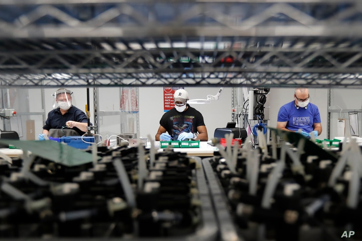FILE - Ford Motor Company line workers put together ventilators that the automaker is assembling at the Ford Rawsonville plant in Ypsilanti Township, Michigan, May 13, 2020.