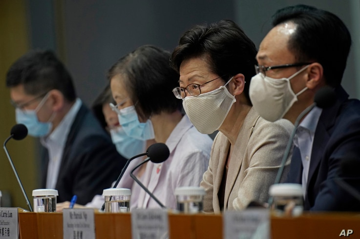 Hong Kong Chief Executive Carrie Lam, second from right, listens to reporters questions during a press conference, July 19, 2020.