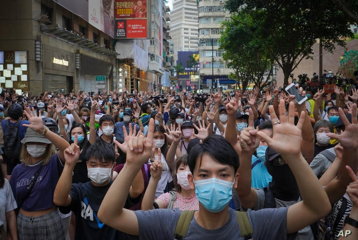 "Protesters against the new national security law gesture with five fingers, signifying the ""Five demands - not one less"" on the anniversary of Hong Kong's handover to China from Britain in Hong Kong, July 1, 2020."