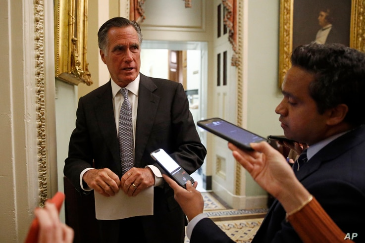FILE - Republican Senator Mitt Romney speaks with members of the media on Capitol Hill in Washington, March 16, 2020.