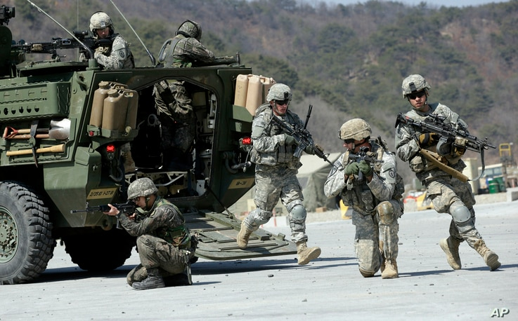 FILE - U.S. Army and South Korean soldiers take their positions during a live-fire exercise as a part of the annual joint military exercises, at the Rodriquez Multi-Purpose Range Complex in Pocheon, South Korea, March 25, 2015.