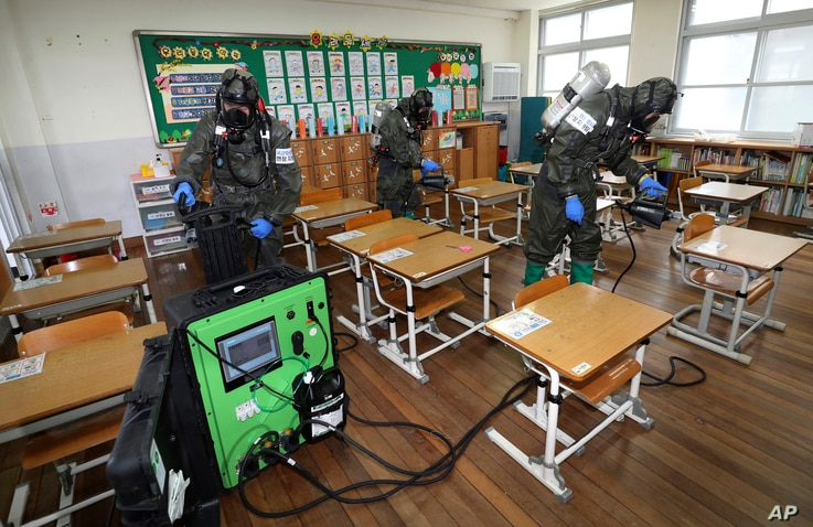 South Korean army soldiers spray disinfectant to help reduce the spread of the new coronavirus in a class at Cheondong elementary school in Daejeon.