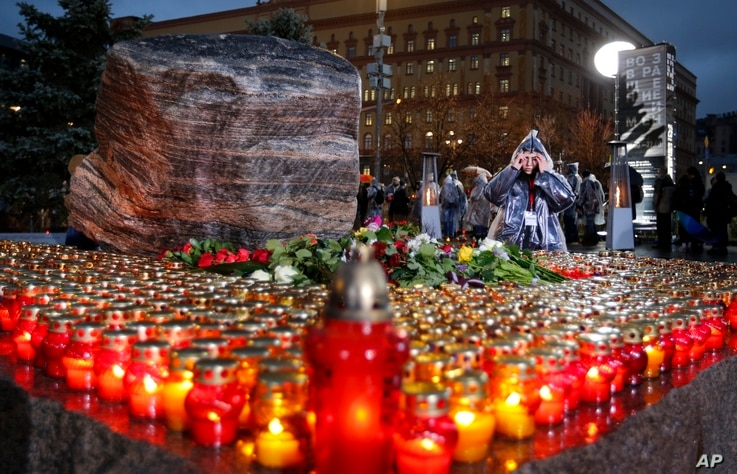 FILE - Flowers and candles are placed at a memorial in Moscow, Russia, Oct. 29, 2019, during a commemoration of victims of Joseph Stalin's purges.