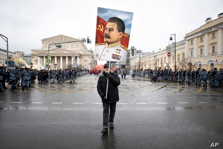 FILE - A supporter carries a portrait of former Soviet dictator Josef Stalin during a rally marking Defenders of the Fatherland Day, in Moscow, Russia, Feb. 23, 2020.