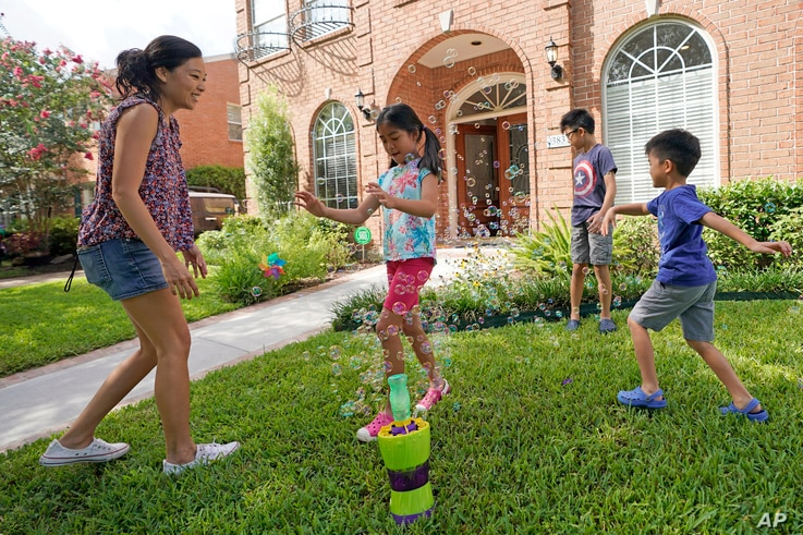 Vicky Li Yip sets up a bubble machine for her children, left to right, Kelsey, 8, Toby, 10 and Jesse, 5, outside their home, July 10, 2020, in Houston, Texas.
