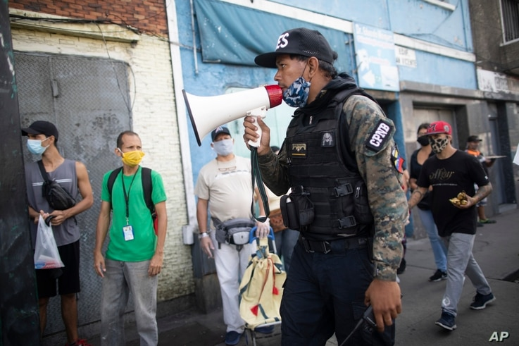 A member of the National Police Action Force uses a megaphone, telling people to return home due to the government-ordered lockdown to curb the spread of COVID-19, in Caracas, Venezuela, July 2, 2020.