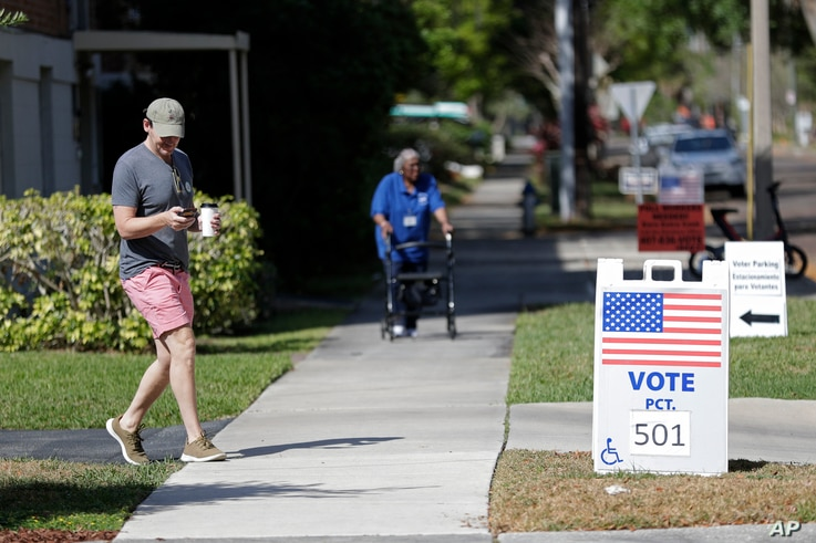 FILE - A young voter, left, leaves a polling station after casting his ballot in Florida's primary election, in Orlando, Florida, March 17, 2020.