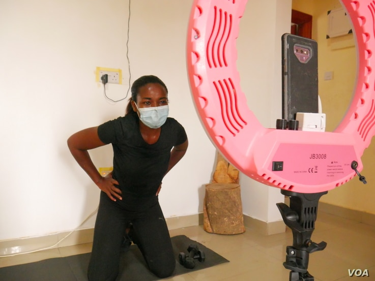 Maabena Antwi used to run popular boot camps for women in Accra; now she does training sessions with them through her phone, from her apartment in Accra, Ghana, July 1, 2020. (Stacey Knott/VOA)