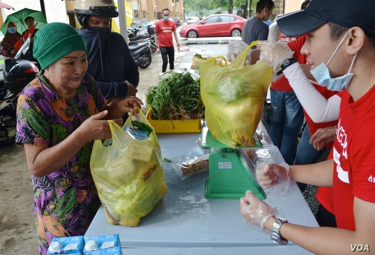 Kechara staff help a woman with a bag of produce at one of the charity's mobile food banks in Kuala Lumpur. (Zsombor Peter/VOA)
