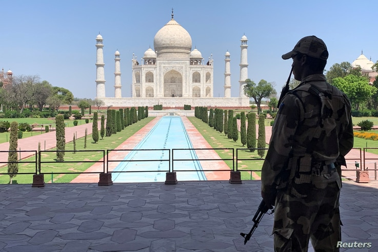 FILE - A security officer stands guard on the empty grounds of the historic Taj Mahal during a coronavirus lockdown, in Agra, India, April 2, 2020.