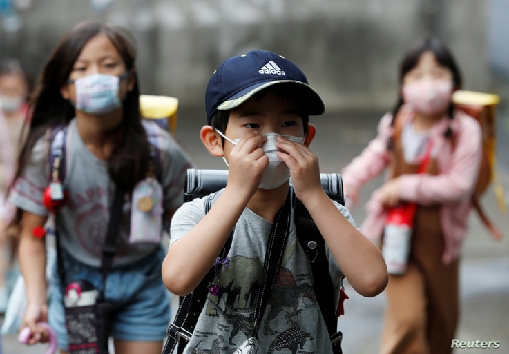 Children, wearing protective masks amid the coronavirus pandemic, arrive at their elementary school, which practices various methods of social distancing, in Funabashi, east of Tokyo, Japan, July 16, 2020.