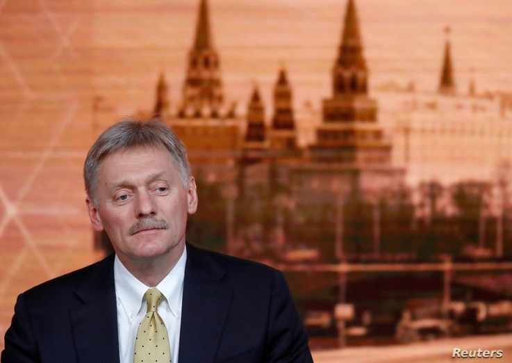 FILE - Kremlin spokesman Dmitry Peskov listens during Russian President Vladimir Putin's annual end-of-year news conference in Moscow, Russia, Dec. 19, 2019.