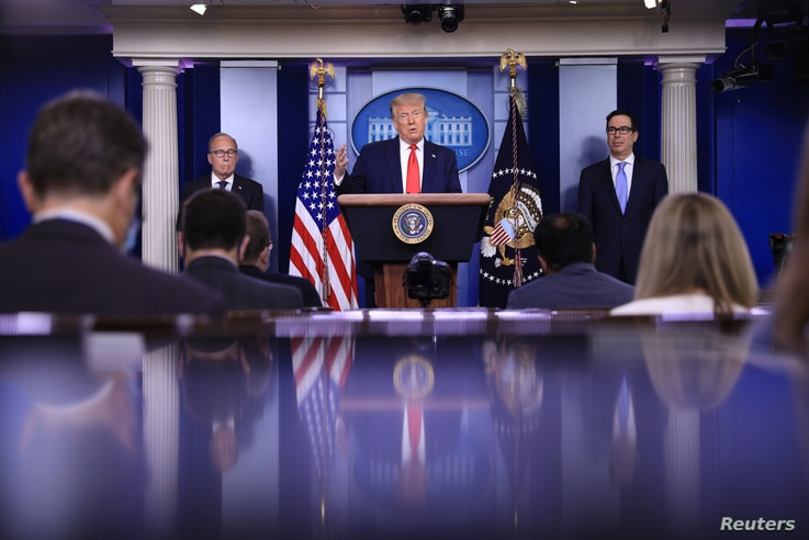FILE - President Donald Trump speaks, flanked by White House economic advisor Larry Kudlow, left, and Treasury Secretary Steven Mnuchin, during a briefing on the U.S. economy in the Brady Press Briefing Room at the White House in Washington, July 2, 2020.