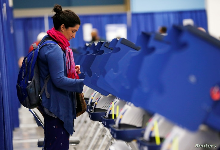 FILE - A young voter casts her ballot during early voting in Chicago, Illinois, Oct. 14, 2016.