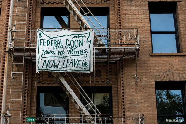 A banner against the presence of federal law enforcement officers is pictured on a fire escape in downtown Portland, Oregon, July 17, 2020.
